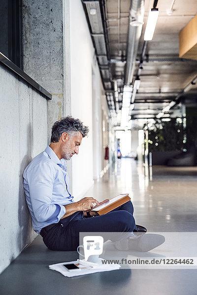 Der reife Geschäftsmann sitzt auf dem Boden und benutzt eine Tablette.