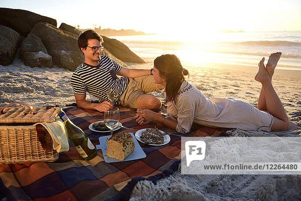 Glückliches Paar beim Picknick am Strand bei Sonnenuntergang Glückliches Paar beim Picknick am Strand bei Sonnenuntergang