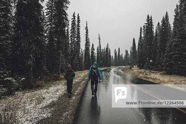 Kanada  British Columbia  Yoho Nationalpark  zwei Männer beim Wandern auf der Yoho Valley Road bei Schneefall