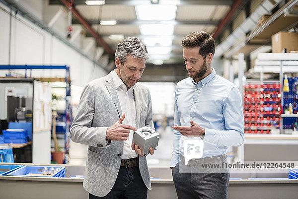 Geschäftsleute beim Treffen mit einem Produkt in der Produktionshalle