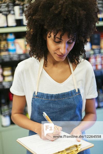 Frau im Laden macht sich Notizen in der Zwischenablage