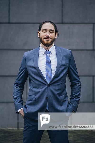 Porträt eines lächelnden Geschäftsmannes im Freien mit geschlossenen Augen