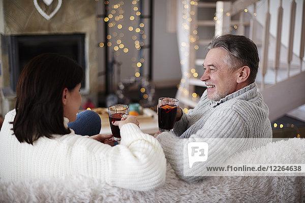 Glückliches reifes Paar mit heißen Getränken im Wohnzimmer