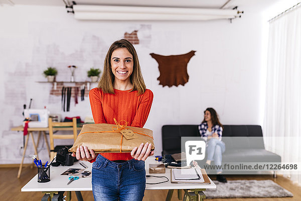 Smiling fashion designer holding a wrapped package in studio