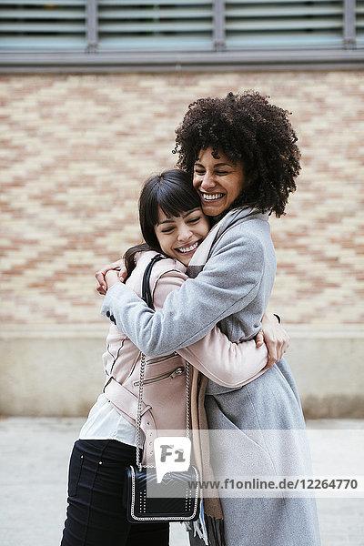 Spanien  Barcelona  zwei glückliche Frauen  die sich in der Stadt umarmen.