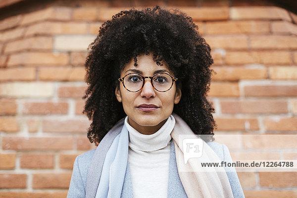 Porträt einer ernsten Frau an der Ziegelwand