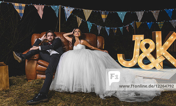 Portrait of wedding couple posing sitting on sofa on a night field party