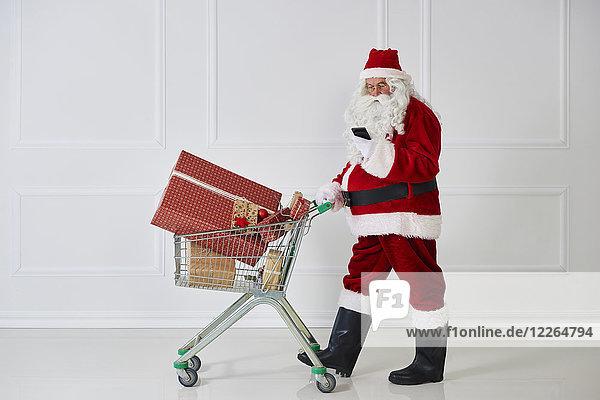 Weihnachtsmann mit Weihnachtsgeschenken im Einkaufswagen beim Blick aufs Handy