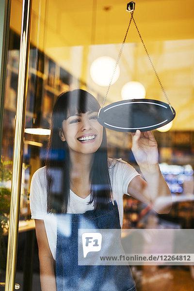 Glückliche Frau  die das Schild im Schaufenster eines Ladens dreht.