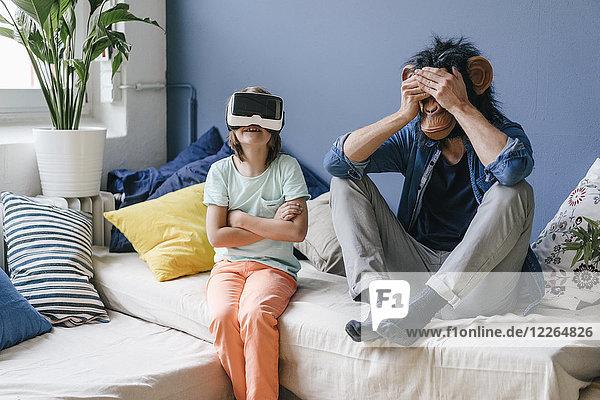 Vater mit Affenmaske sitzend neben Sohn mit VR-Brille zu Hause