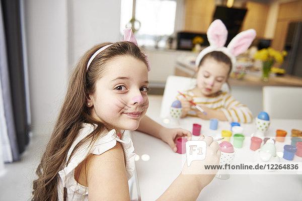 Porträt eines lächelnden Mädchens mit Schwester am Tisch sitzend Ostereier malend