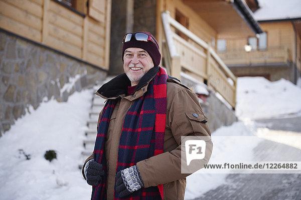 Porträt eines lächelnden älteren Mannes im Bergdorf im Winter