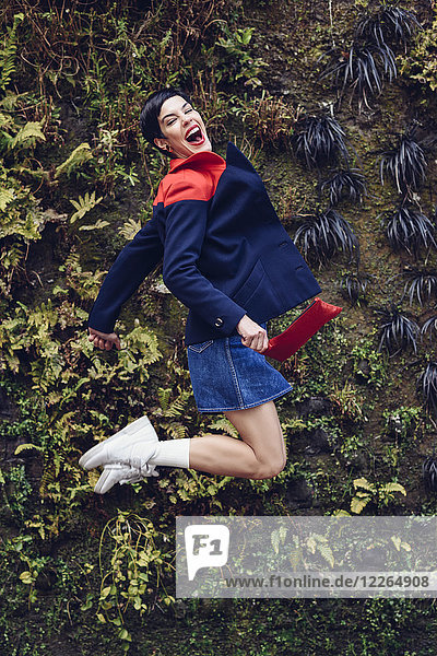 Portrait of fashionable young woman jumping in the air in front of Living Wall