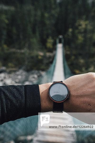 Männerhand mit Uhr vor der Drehbrücke
