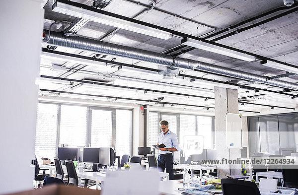 Erwachsener Geschäftsmann im Großraumbüro mit Notizbuch