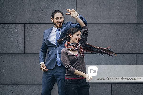 Fröhlicher Geschäftsmann und Frau tanzen im Freien