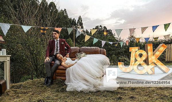 Braut auf dem Sofa liegend mit Bräutigam auf dem Feld