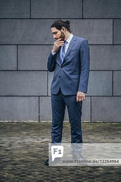 Ein seriöser Geschäftsmann  der im Freien steht und nach unten schaut.