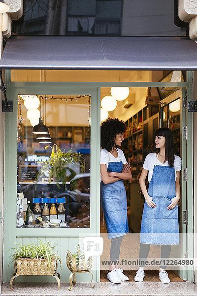 Zwei lächelnde Frauen stehen in der Eingangstür eines Ladens.