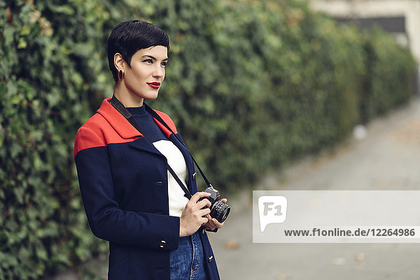 Portrait of fashionable young woman with camera