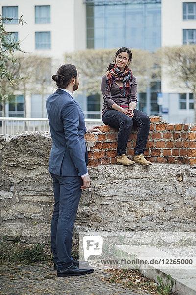 Frau sitzt auf einer Wand vor dem Bürogebäude und lächelt den Geschäftsmann an.