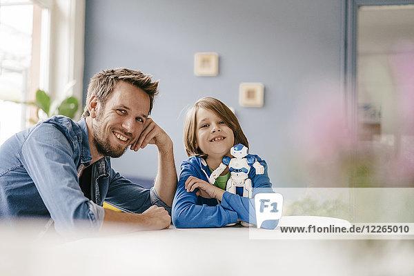 Porträt eines glücklichen Vaters und Sohnes mit Roboter zu Hause