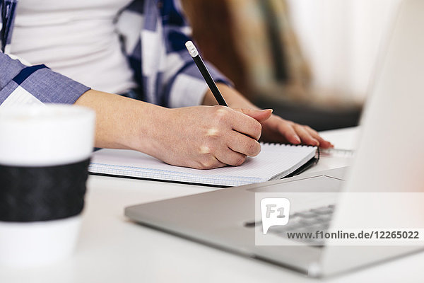 Close-up of woman with laptop taking notes at desk