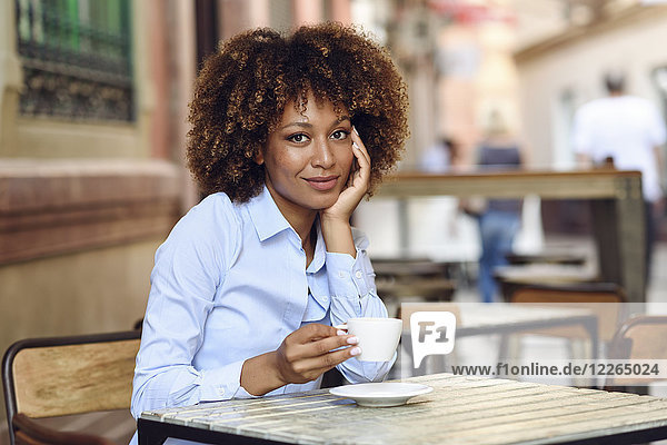 Portrait of smiling woman with afro hairstyle sitting in outdoor cafe