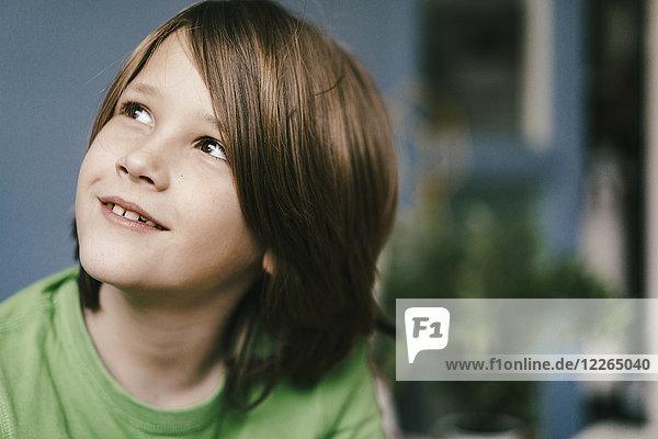 Porträt eines lächelnden Jungen  der nach oben schaut