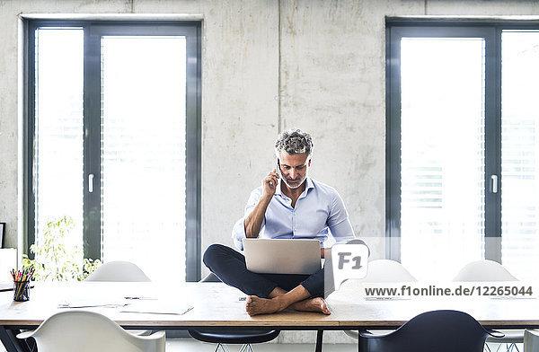 Reife Geschäftsleute sitzen barfuß auf dem Schreibtisch im Büro mit Handy und Laptop