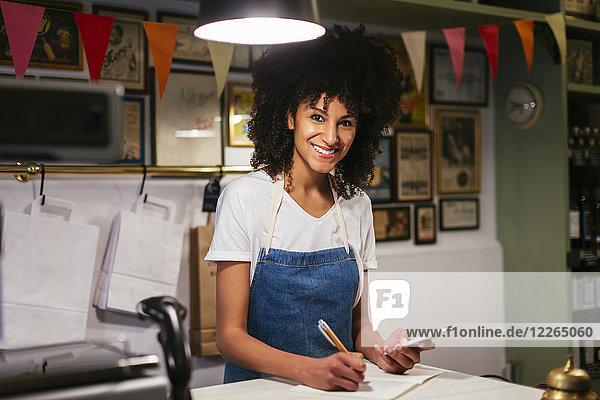 Porträt einer lächelnden Frau mit Handy und Notizbuch im Laden