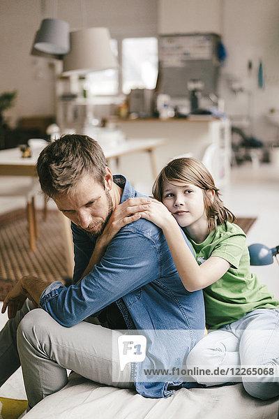 Sohn tröstet traurigen Vater zu Hause