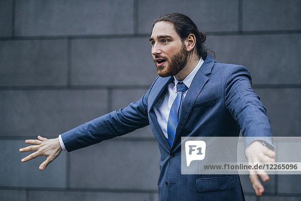Porträt eines Geschäftsmannes  der im Freien steht und gestikuliert.