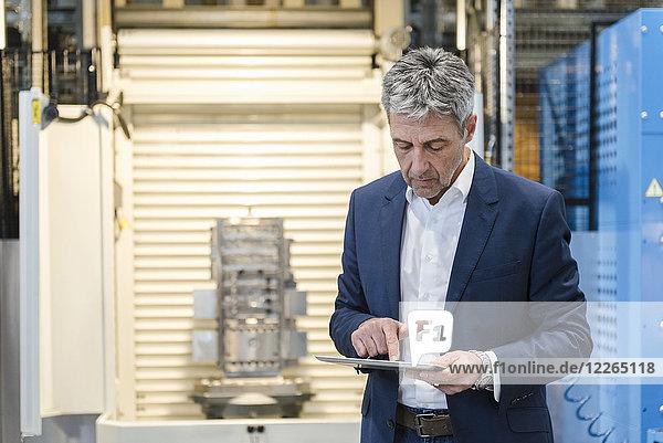 Geschäftsmann mit Tablette in der Produktionshalle