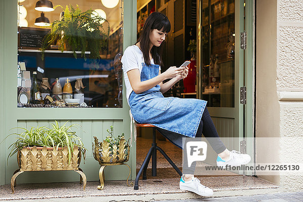 Woman sitting on stool using cell phone at entrance door of a store