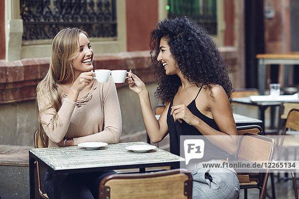 Zwei glückliche Freunde beim Kaffeetrinken im Straßencafé