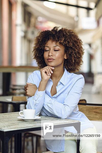 Entspannte Frau mit Afro-Frisur sitzend im Outdoor-Café