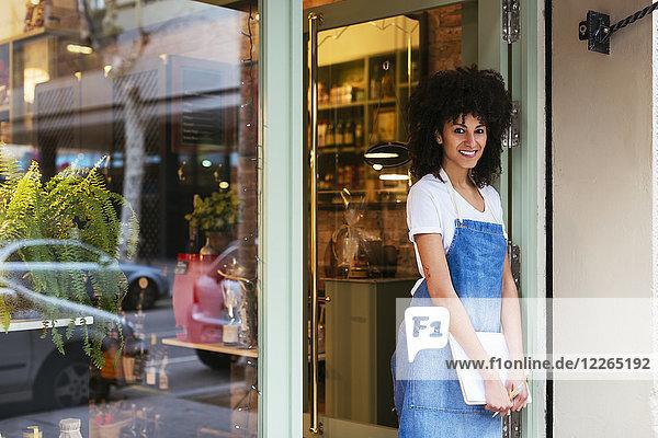 Porträt einer lächelnden Frau  die in der Eingangstür eines Ladens steht