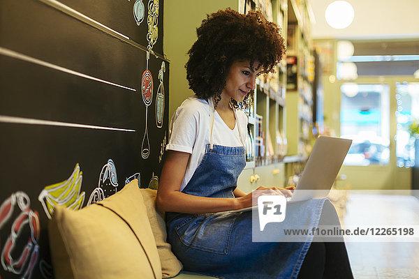 Frau mit Laptop in einem Geschäft