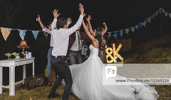 Happy bride and friends with arms raised dancing and having fun on a night field party