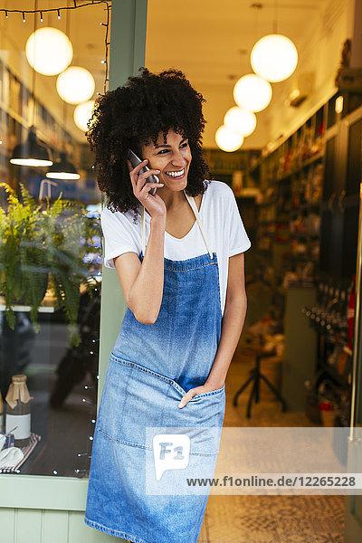 Glückliche Frau am Handy in der Eingangstür eines Ladens stehend