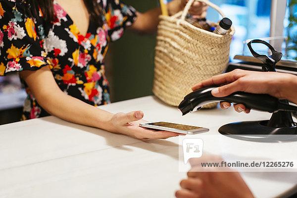 Nahaufnahme des bargeldlosen Bezahlens mit dem Smartphone am Schalter eines Ladens