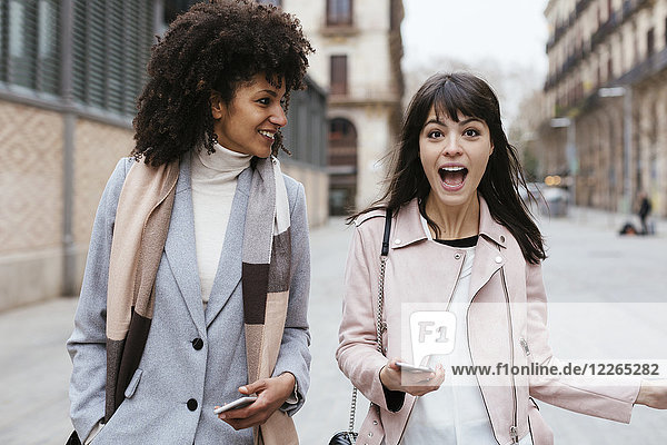 Spanien  Barcelona  zwei Freundinnen mit Mobiltelefonen in der Stadt