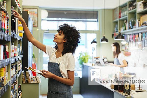 Frau mit Klemmbrett im Ladenregal