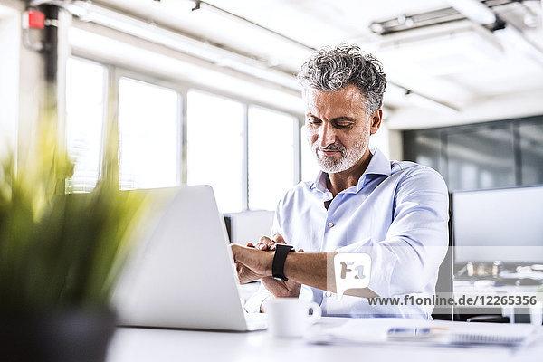Der reife Geschäftsmann sitzt am Schreibtisch im Büro und schaut auf smartwatch