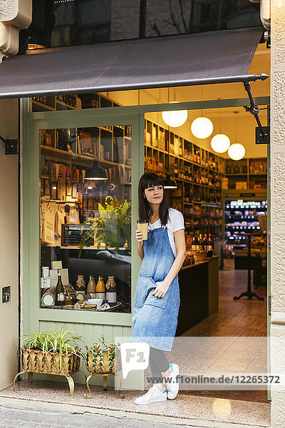Frau steht an der Eingangstür eines Ladens mit Kaffee zum Mitnehmen