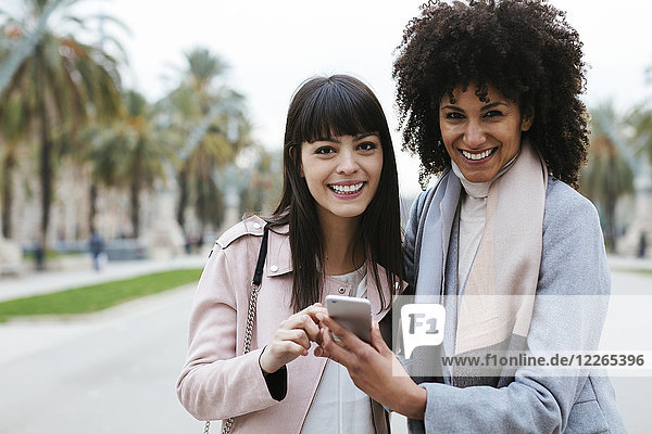 Spain  Barcelona  portrait of two happy women with cell phone on promenade