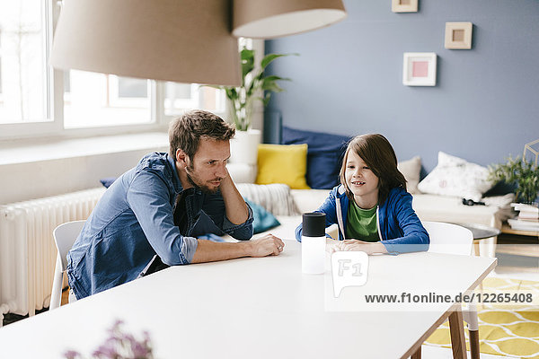 Vater und Sohn bei der Suche nach innovativen Produkten auf dem Tisch zu Hause