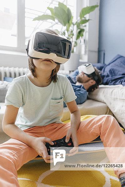 Junge und Vater mit VR-Brille beim Videospiel zu Hause