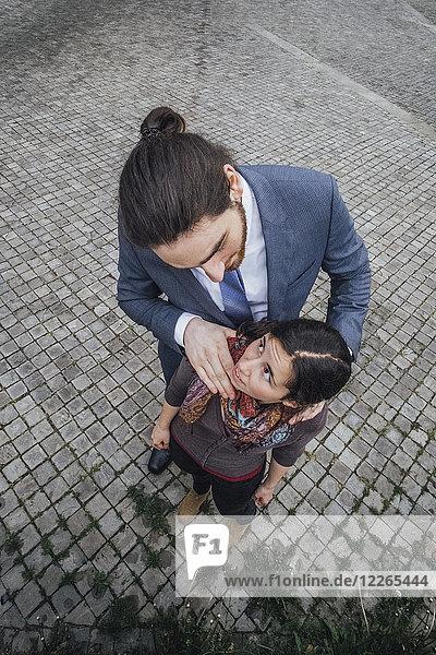 Geschäftsmann steht auf Kopfsteinpflaster und schaut die Frau mit der Hand auf den Schultern an.
